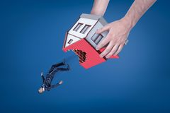 Close-up of man`s hands holding house with hole in roof upside down and dropping out little businessman. stock photos