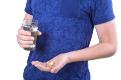 A close-up man`s hands holding pills. A sick guy isolated on a white background. A male taking meds. Drug addiction. A man standing and holding medicine Stock Photos