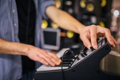 Close up of man`s hands on keyboard. Guy turn sound on. He stand in room. Many sound speakers are behind him. Close up of man`s hands on keyboard. Guy turn royalty free stock image