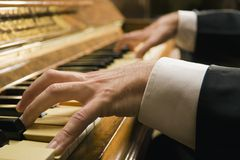 Close-up of a man`s hands playing a piano Stock Photos