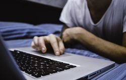 Close up of man`s hands using computer, surfing on internet and relaxing on bed royalty free stock images