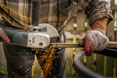 Close up of man& x27;s hands using grinding machine to grind metal. At the backyard Royalty Free Stock Photo