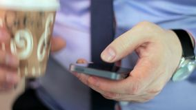 Close-up man's hands using mobile phone touchscreen and cofee. Close-up man's hands using smartphone touchscreen and drink cofee stock video footage