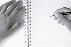 Close up of man`s hands writing in spiral notepad. Soft focus Royalty Free Stock Photo