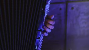 Close-up of a man`s left hand playing on a black accordion. stock video footage