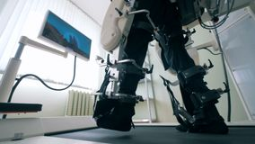 Close up of man`s legs in bonds of a training machine during walking exercises. Electronic medical robotic for stock footage