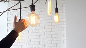 Close-up of man`s palm touching large electric lamp bulb in light room against white brick wall. Media. Electricity. Close-up of man`s palm touching large stock photography