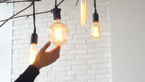 Close-up of man`s palm touching large electric lamp bulb in light room against white brick wall. Media. Electricity. Close-up of man`s palm touching large royalty free stock images