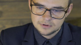 Close up of man's portrait looking on screen and wondering stock video footage