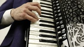 Close-up of a man`s right hand playing on a black accordion. stock footage