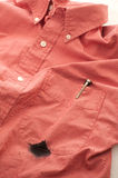 Close up of Man's Stained Shirt with Broken Pen. A closeup of a reddish colored man's shirt stained with the ink of the broken pen. Vertical version with pen stock image