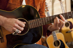 Close-up of man's torso practicing with guitar Stock Image