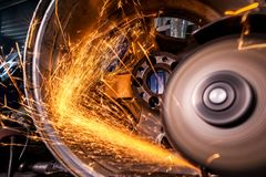 A close-up of a car mechanic. Close-up of a man sawing   bearing metal with a hand circular saw, bright flashes flying in different directions, in the background royalty free stock photos