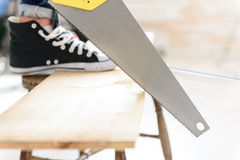 Close up of man sawing wood board Stock Images