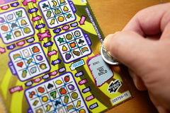 Close up man scratching lottery ticket on bonus section. Stock Images