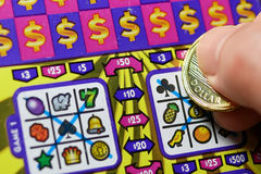 Close up man scratching lottery ticket. Royalty Free Stock Images