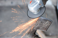 Close up of a man sharpen an ax using electric grinder Stock Images
