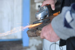 Close up of a man sharpen an ax using electric grinder Royalty Free Stock Photos