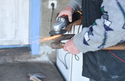 Close up of a man sharpen an ax using electric grinder Stock Photo