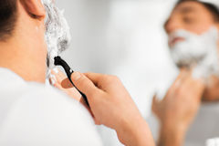 Close up of man shaving beard with razor blade Stock Images