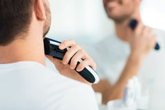 Close up of man shaving beard with trimmer Stock Photos