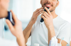 Close up of man shaving beard with trimmer. Beauty, shaving, grooming and people concept - close up of young man looking to mirror and shaving beard with trimmer Royalty Free Stock Photos