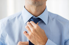 Close up of man in shirt adjusting tie on neck Royalty Free Stock Image