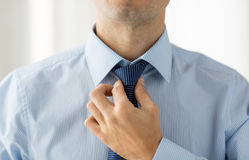 Close up of man in shirt adjusting tie on neck. People, business, fashion and clothing concept - close up of man in shirt dressing up and adjusting tie on neck Stock Images