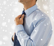 Close up of man in shirt adjusting tie on neck Stock Image