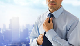 Close up of man in shirt adjusting tie on neck Stock Images