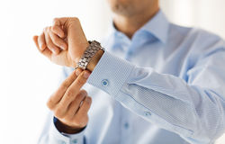 Close up of man in shirt fastening wristwatch Royalty Free Stock Image