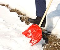 Close-up of man shoveling snow with red shovel. Cleaned path in background Royalty Free Stock Image