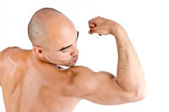 Close up on a man showing and kissing his biceps. Stock Photography
