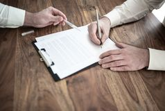 Man signing contract at wooden desk with other person pointing at document. Close-up of man signing contract at wooden desk with other person pointing at stock images