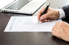 Close-up man signing of on resume form. Royalty Free Stock Images