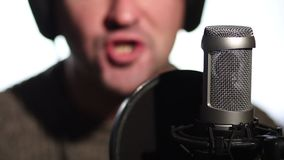 Close up man singing into a condenser microphone. stock footage