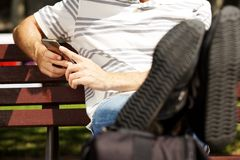 Close up man sitting on bench outdoors with legs on bag and using mobile phone. Close up portrait of young man sitting on bench outdoors with legs on bag and Stock Photos