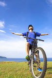 Close-up man sitting on a  mountain bike and open arms to relax Royalty Free Stock Photography