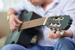 Man playing guitar at home royalty free stock image
