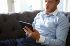 Close Up Of Man Sitting On Sofa Using Digital Tablet Stock Images