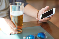 Close up of man with smartphone and beer at pub. People, leisure and technology concept - close up of man with smartphone drinking beer and reading message at Royalty Free Stock Photos
