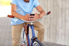 Close up of man with smartphone and bike on street Stock Photos
