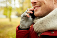 Close up of man with smartphone calling in autumn Royalty Free Stock Images