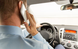 Close up of man with smartphone driving car Stock Photo