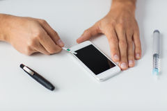 Close up of man with smartphone making blood test Stock Images