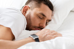 Close up of man with smartwatch sleeping in bed Royalty Free Stock Photos