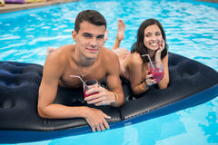 Close-up man and a smiling woman lying on a mattress in the pool with cocktails enjoying the holiday. Focus on the man Royalty Free Stock Images