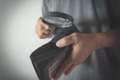 Close-up man standing and holding magnifying glass for looking. In the wallet empty of money Royalty Free Stock Photography