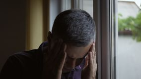 Close-up of a man standing at the window, holding his hands over his head suffering from a headache. stock video