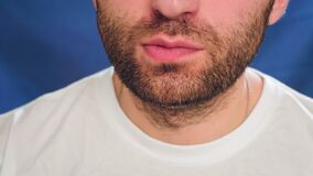 Close-up, a man with stubble eating french fries. It does not lead a healthy lifestyle, impairs health and metabolism